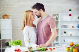 The couple in love kisses in kitchen