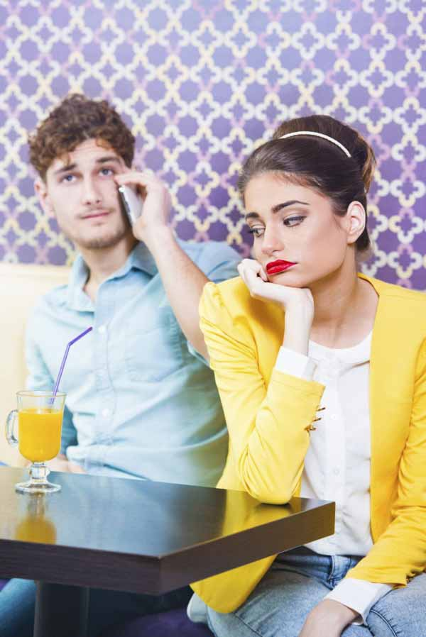 A girl is bored with a man talking over the phone on a date