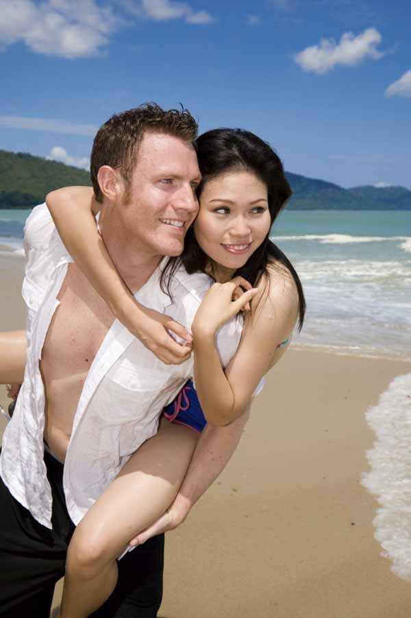 playful couple at the beach looking sideways