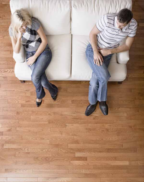 Man and a woman sit distantly on the ends of love seat.