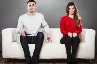 Guy sitting near attractive young woman on sofa and making hand gesture walking with finger to girl