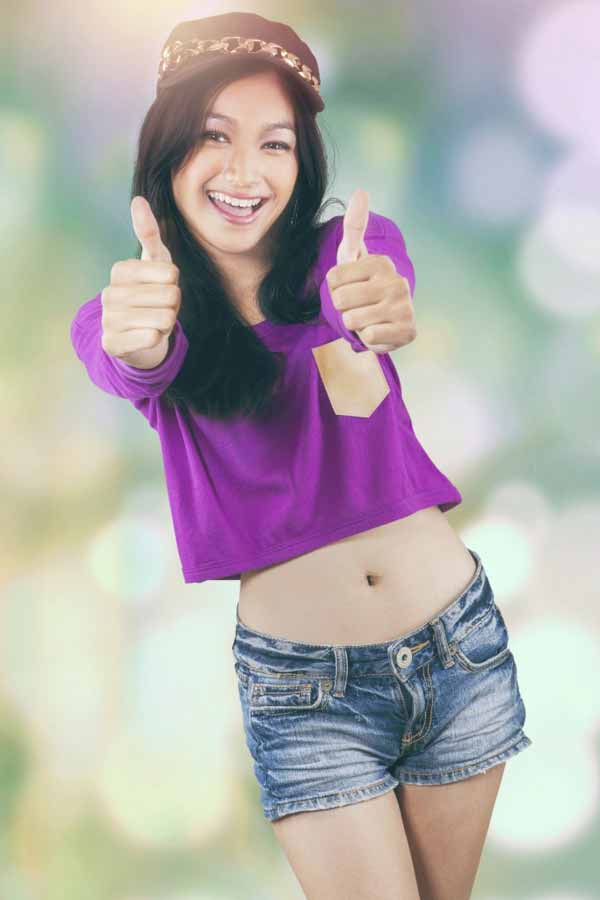 Happy Phillipine female hipster with modern clothes, showing thumbs up on the camera,