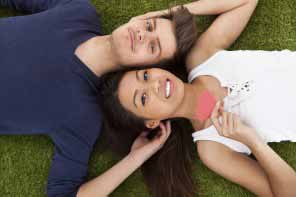 young couple lying on grass in park