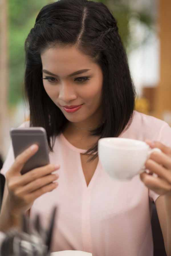 Smiling young woman reading text message