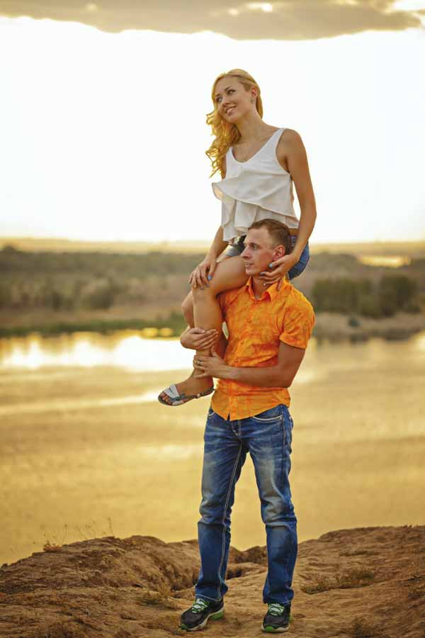 Loving couple on the river bank.