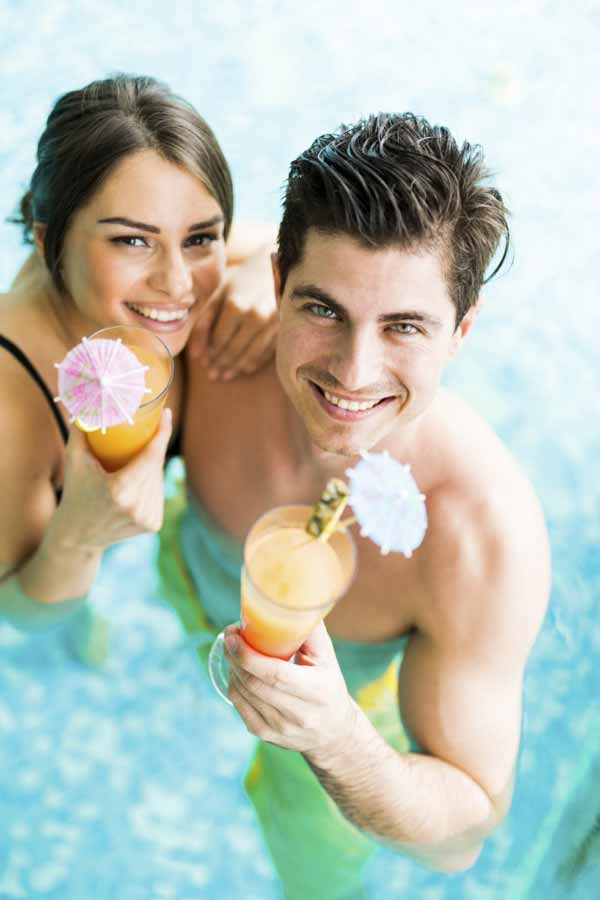 beautiful young couple smiling and drinking a cocktail