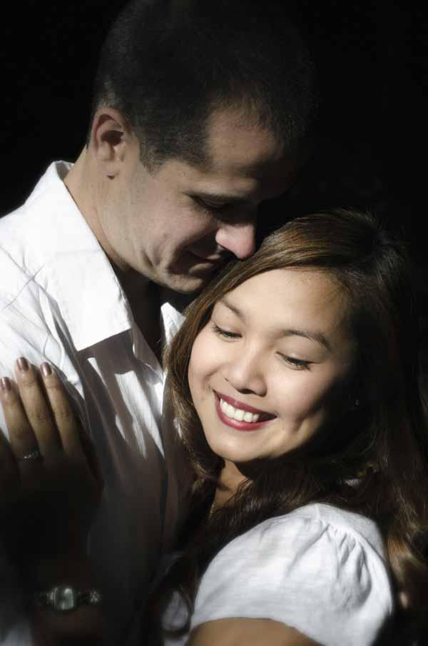a Western man hugging smiling Filipina