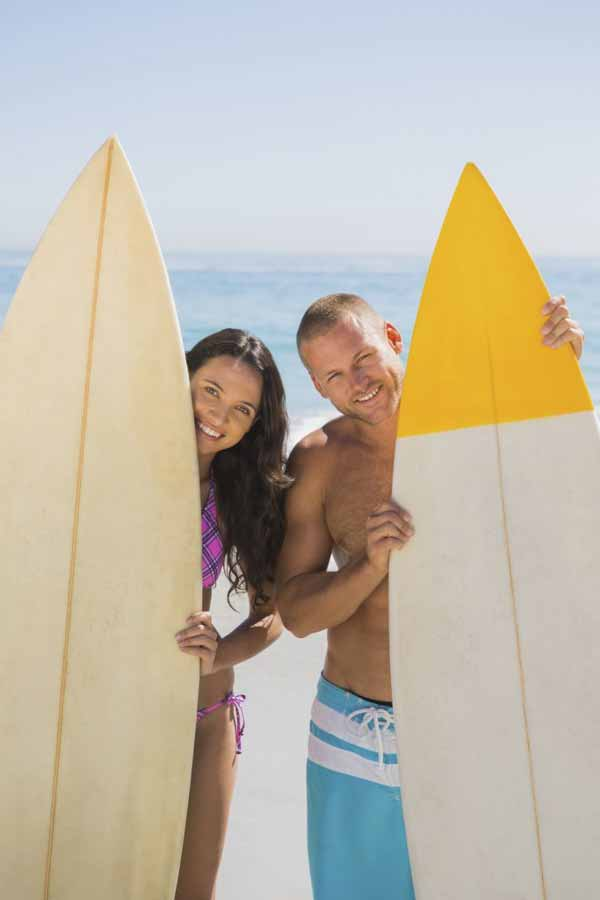young surfer couple on the beach