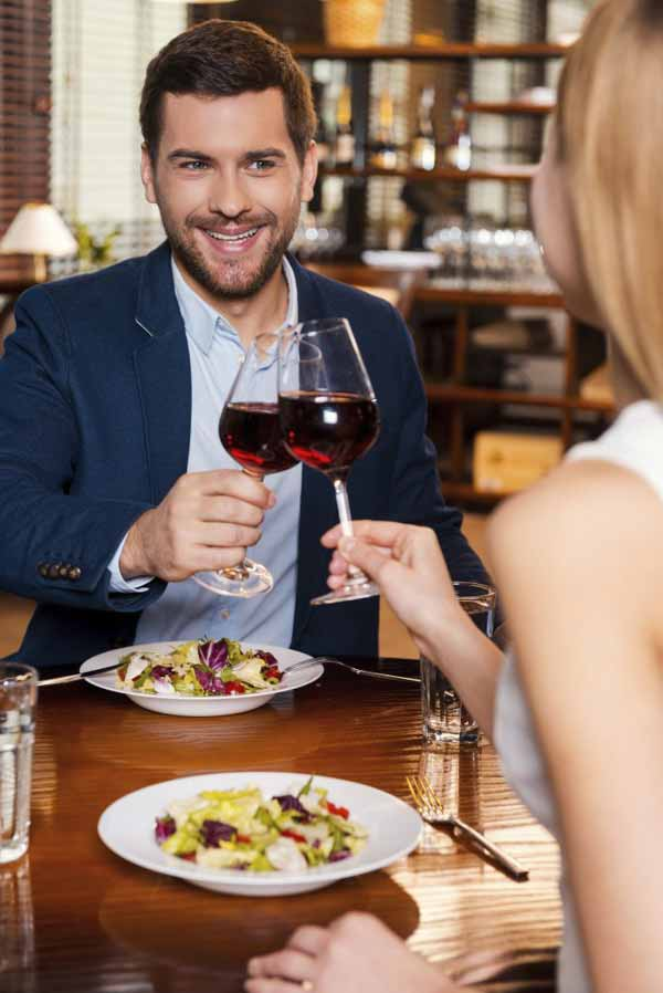 Beautiful young loving couple toasting with red wine