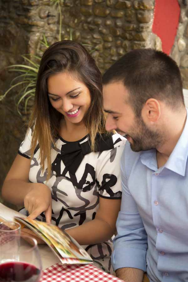 Happy young couple reading a menu in a restaurant.