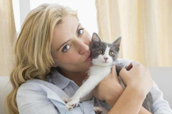 a beautiful blond lady kissing her cat