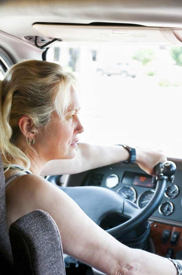 a blonde woman truck driver in her truck