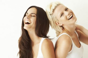 two smiling girls a blonde vs brunette