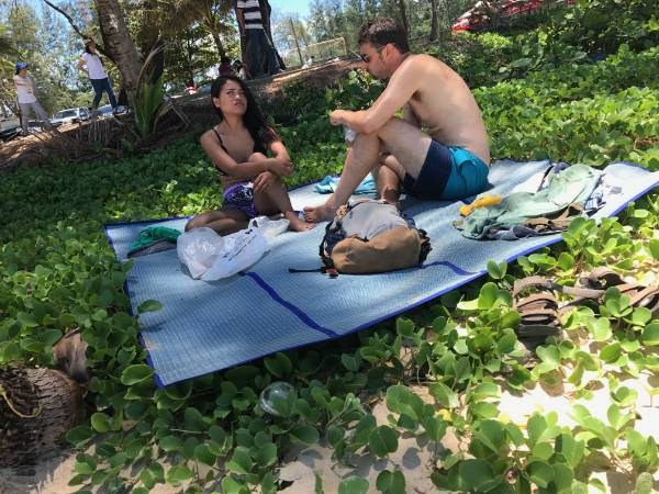 American man and Thai girl on the beach