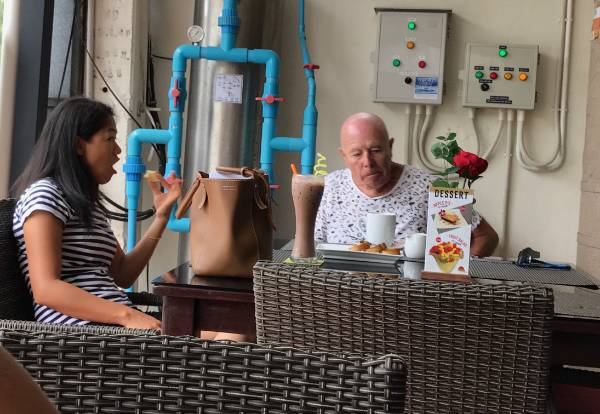 Senior Australian man and Thai woman eating in restaurant