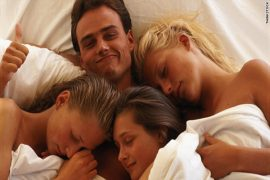 a happy man in bed surrounded by three girls