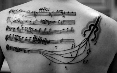 male's back with music notes tatoo